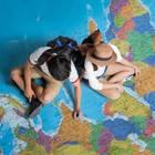 Zwei junge Frauen sitzen auf großer Weltkarte