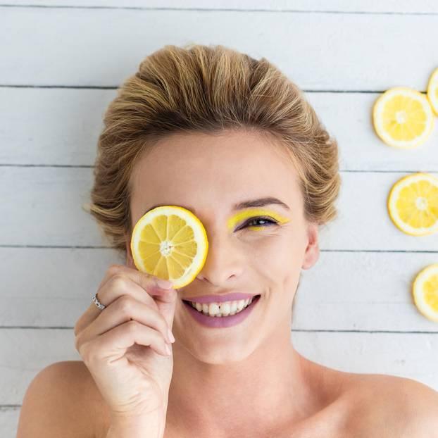 Haare natürlich färben: Blonde Frau mit Zitrone vor dem Auge