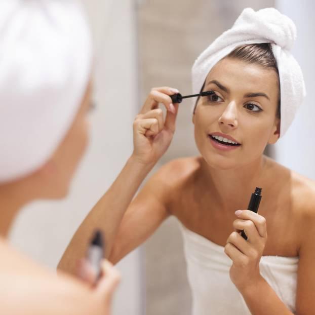 Frau trägt Mascara im Spiegel auf
