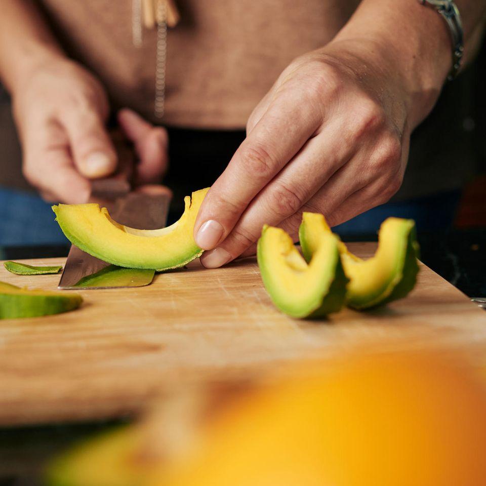 Koch schneidet Avocado in Scheiben