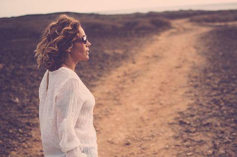 In welchen Lebensjahren altert man besonders: Frau steht auf Feld