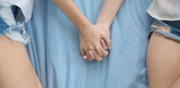 Frauen halten Händchen im Bett