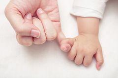 Baby hält kleinen Finger der Mutter