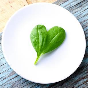 Herzförmiges Spinatblatt auf Teller