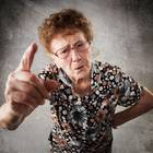 Ältere Frau hebt den Finger in Richtung der Kamera