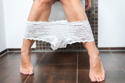 Frau auf Toilette mit heruntergelassenem Höschen