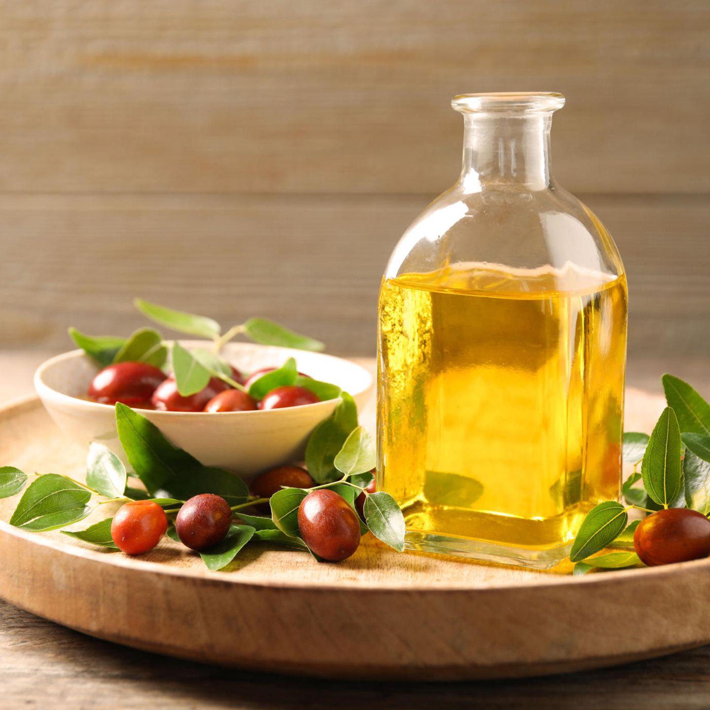 Jojobaöl: Flasche mit Jojobaöl und Samen auf Holzschale