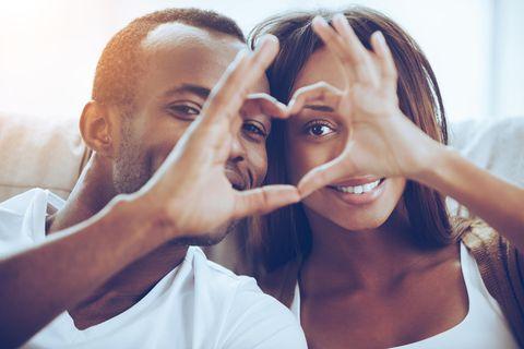 Junges Paar bildet ein Herz mit Fingern