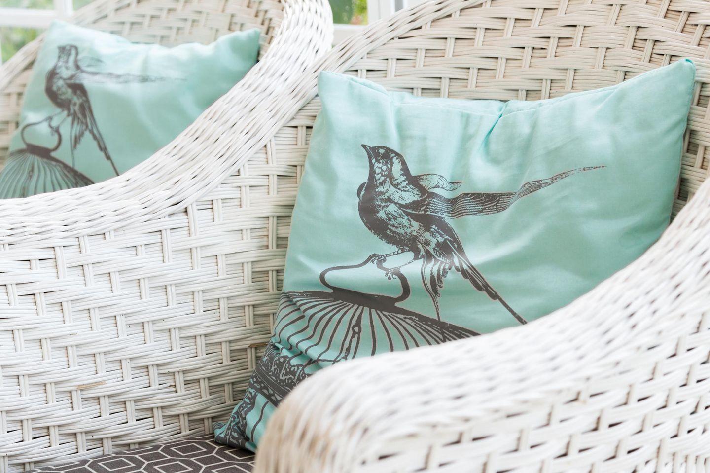 Kissen mit Vogelmotiv auf Stuhl