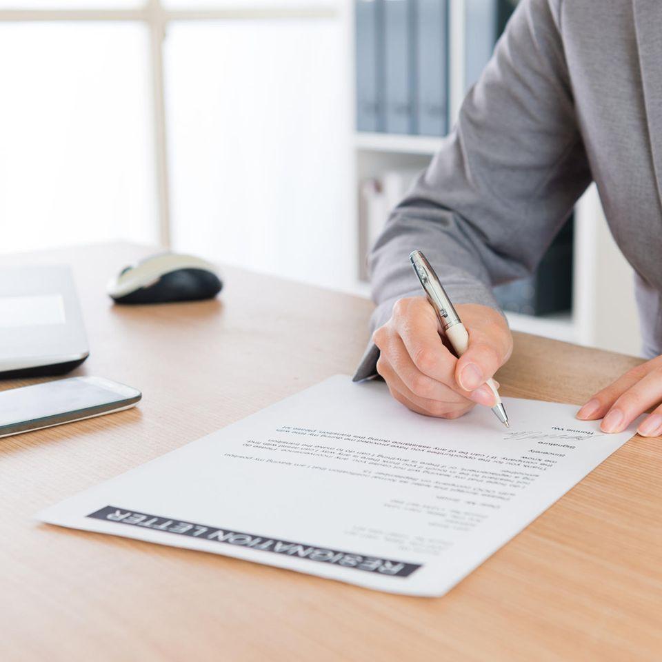 Bewerbung schreiben lassen: Frau unterschreibt Dokument
