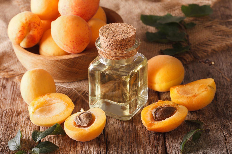Aprikosenkernöl: Kleine Flasche mit Öl und Aprikosen darum