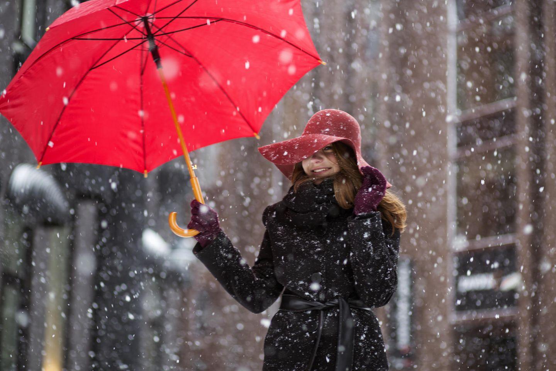 Neujahrsvorsätze, die dich glücklicher machen: Eine fröhliche Frau mit Regenschirm im Schnee