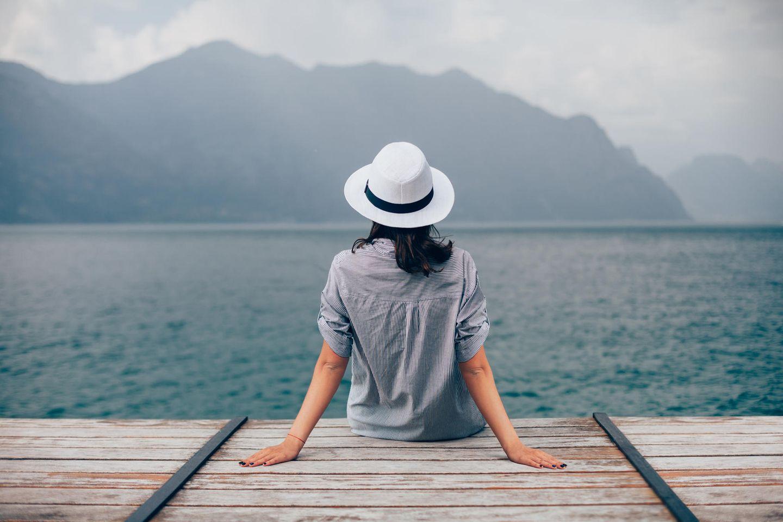 Horoskop: Eine Frau sitzt auf einem Steg am See