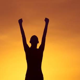 Frau reckt die Arme zum Himmel