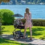 Frau im Sommerkleid schiebt Kinderwagen durch Park