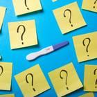 Schwangerschaftstest umgeben von Fragezeichen