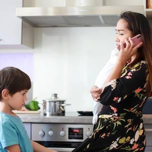 Frau am Telefon und genervtes Kind