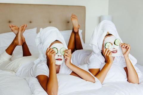 Neujahrs-Skin-Detox: zwei Frauen mit Gesichtsmasken und Gurkenscheiben auf den Augen