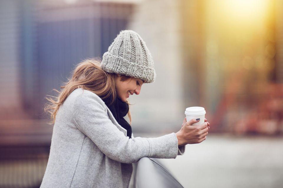 Murmel-Trick: Eine fröhliche Frau mit Coffea-To-Go-Becher