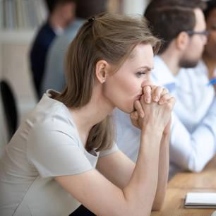 Konzentrationsschwäche: Grübelnde Frau sitzt am Schreibtisch