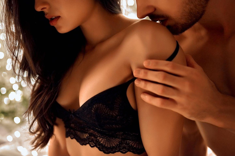 Mann küsst Frau auf die Schulter