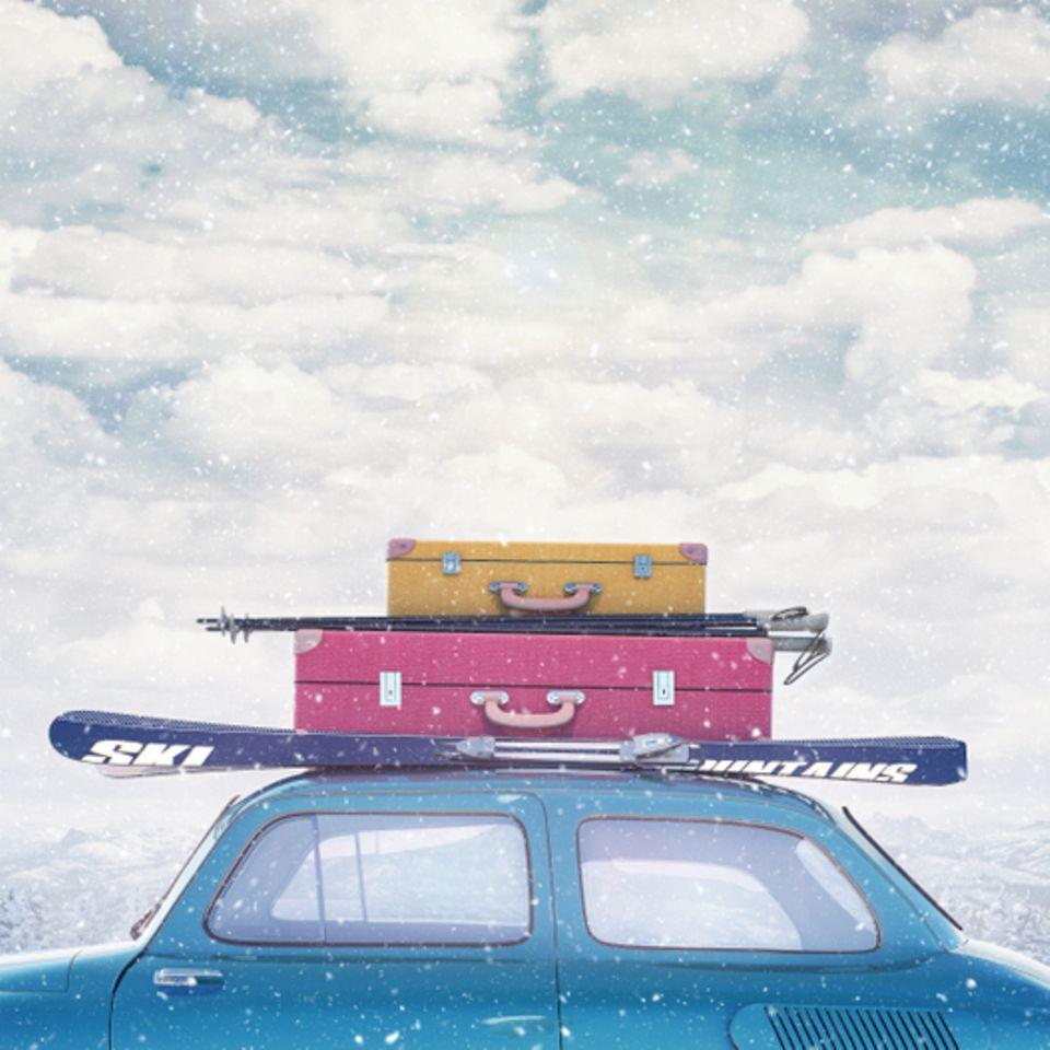 Packliste für den Skiurlaub: Auto mit Koffern und Skiern auf dem Dach