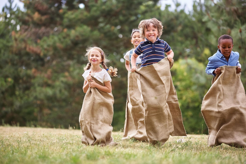 Spiele für den Kindergeburtstag: Kinder beim Sackhüpfen