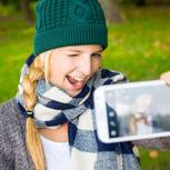 Bewerbungsfoto selber machen: Frau macht lustiges Selfie