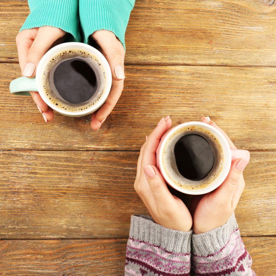Deshalb solltest du morgens auf den Kaffee verzichten: Frauen halten Kaffeetasse fest