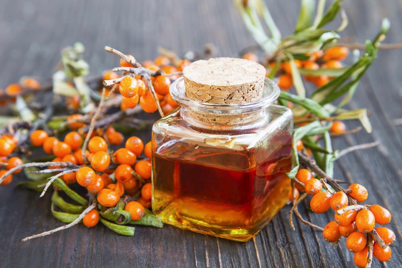 Sanddornöl: Öl in Glasbehälter neben Früchten