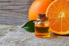 Orangenöl in der Flasche und Orangenhälften