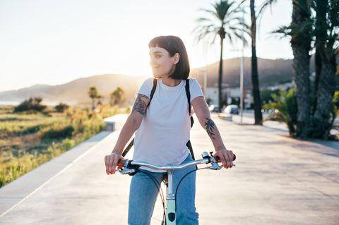 Selbstoptimierung: Eine zufriedene junge Frau auf dem Fahrrad