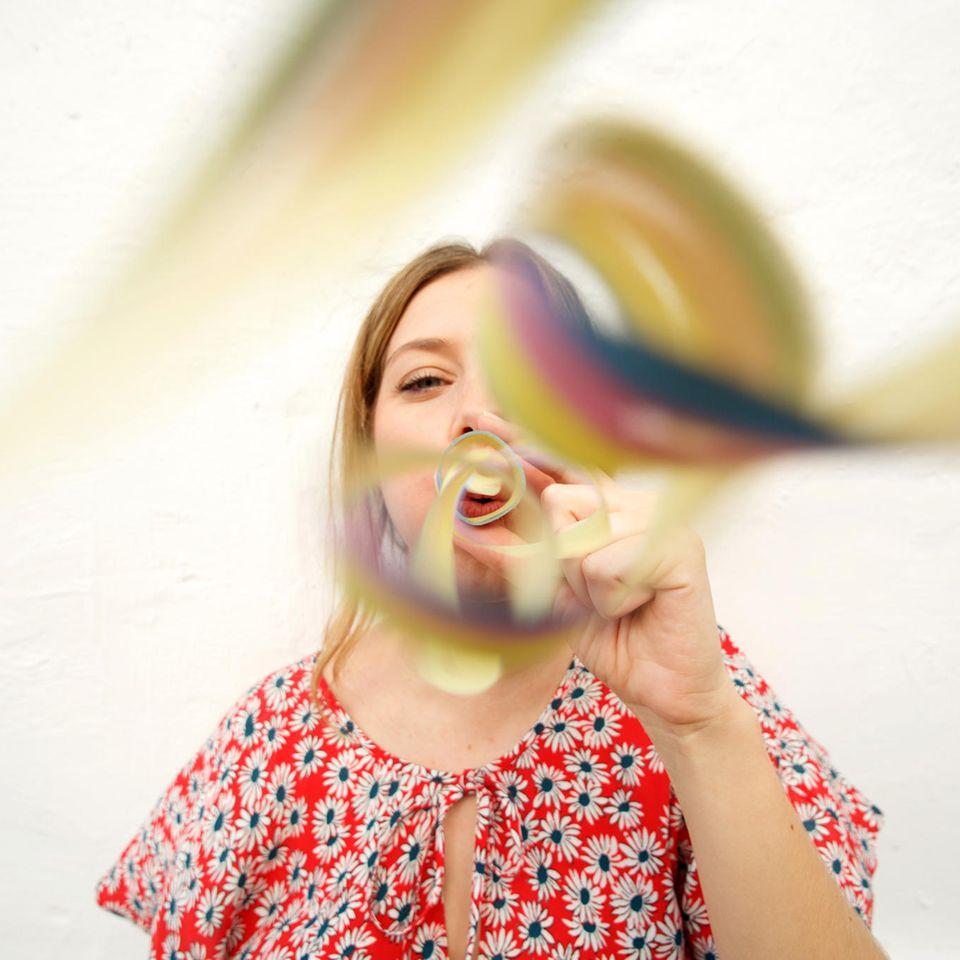 Leben ändern leicht gemacht - eine Anleitung: Frau pustet Luftschlangen