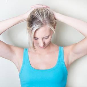 Frau in Tanktop dehnt ihren Nacken