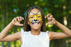Tiger schminken: Mädchen mit geschminktem Tiger-Gesicht