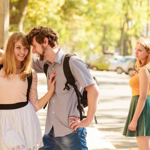 Horoskop: Eine junge Frau schaut neidisch zu einem Pärchen