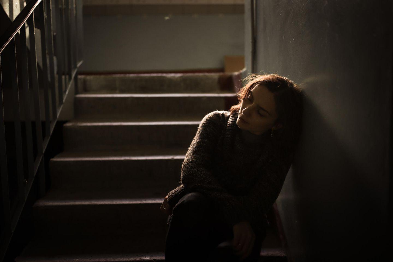 Frau sitzt trauernd auf Treppe