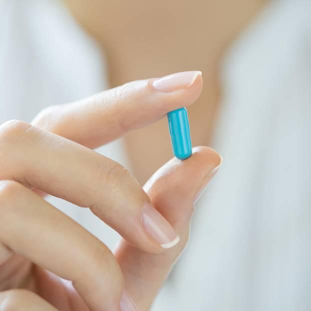 Arzt hält blaue Pille zwischen zwei Fingern