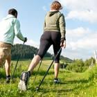 Mann und Frau beim Nordic-Walking auf einer Wiese