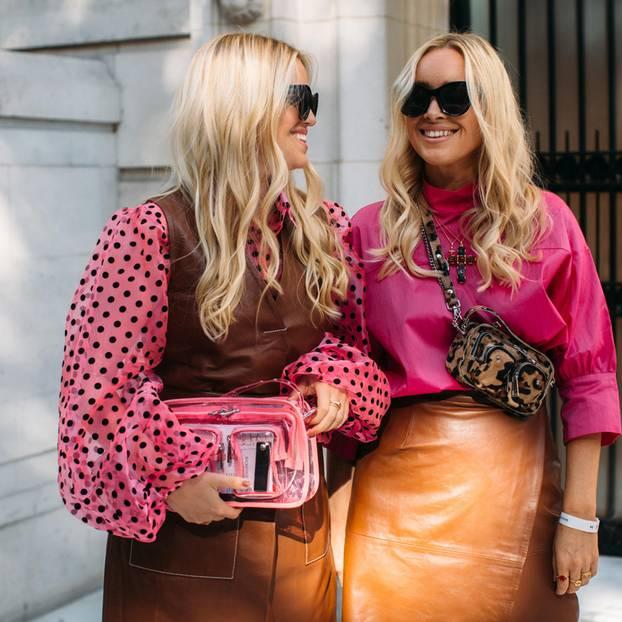 Organza-Puffärmel: Zwei blonde Frauen, die eine trägt eine pinke Bluse mit Organza-Puffärmeln und Polka-Dots