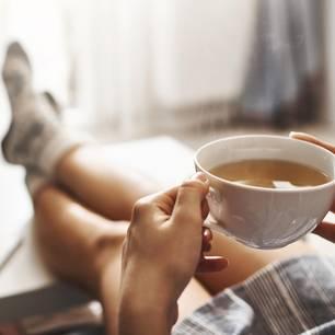 Entschleunigung: Eine Frau trinkt Tee und legt die Füße auf den Tisch