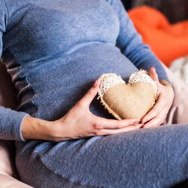 Schwangere Frau mit herzförmigem Kissen auf Bauch