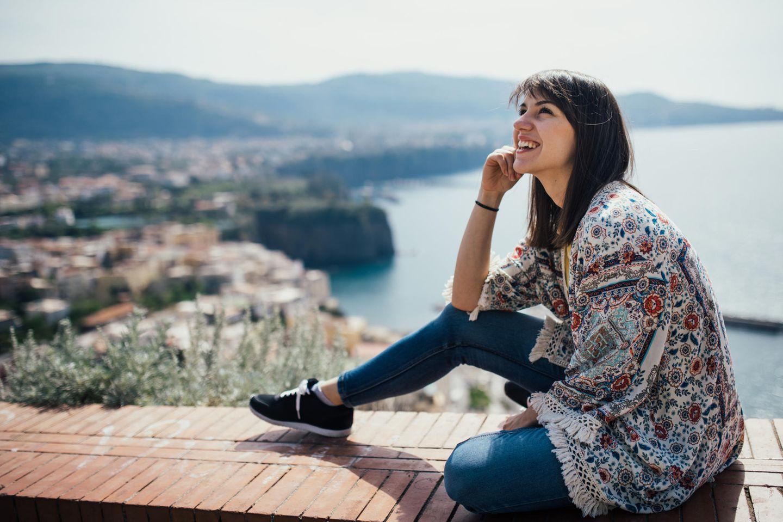 Tipps, wie du Geld sparst und glücklicher wirst: Eine glückliche Frau im Urlaub in Italien
