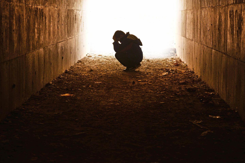 Jugendlicher hockt in Tunnel