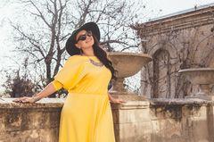 Frau in gelbem Maxikleid und Sonnenhut