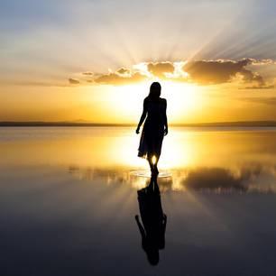 Horoskop: Eine Frau am Meer bei Sonnenaufgang