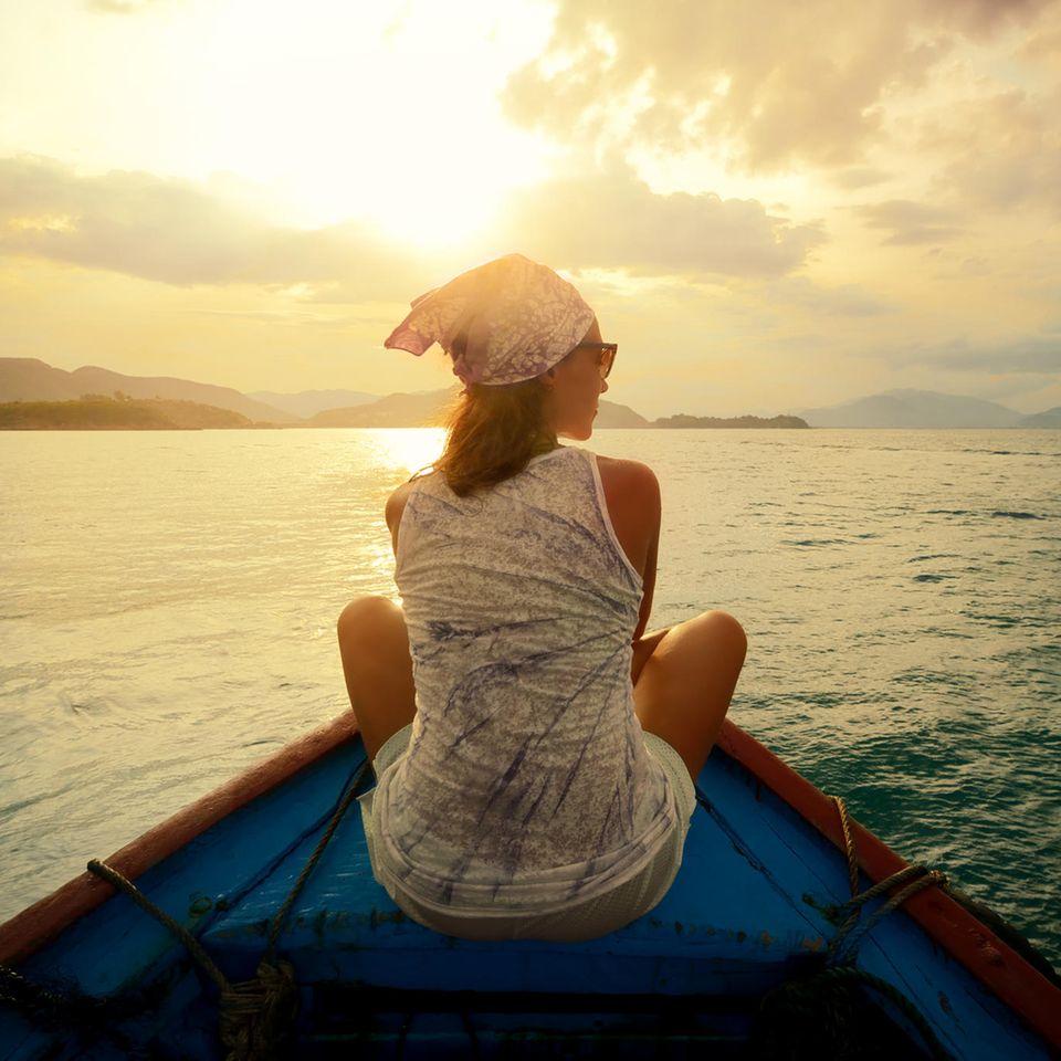 Lebenstraum: Eine junge Frau auf einem kleinen Boot in einem See