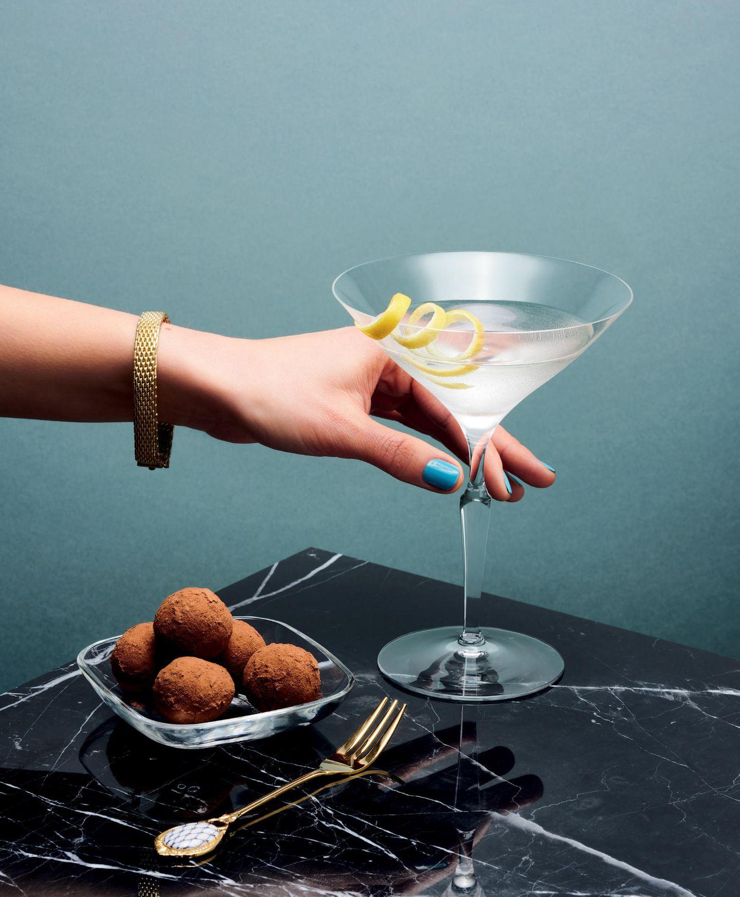 Vesper  für 1 Cocktail:  3 cl Gin, eisgekühlt  2 cl Wodka, eisgekühlt  1 cl Vermouth Dry oder Lillet  Eis  Zitronenschale  1. Den Gin mit Wodka, Vermouth Dry oder Lillet und dem Eis in einem Shaker kräftig schütteln.  2. In ein eisgekühltes Martiniglas abseihen und mit der Zitronenschale garnieren.  Safran-Orangen-Marzipan-Bällchen  für ca. 25 Kugeln:  180 g Puderzucker  200 g Mandelgrieß  0,2 g Safran  1 Vanilleschote  1 Orange (Abrieb und Saft)  10 EL dunkler Backkakao  1. Den Puderzucker in eine Schale sieben.  2. Mandelgrieß, Safran, Mark der Vanilleschote, Abrieb und 4 EL Saft der Orange dazugeben und alles gut verkneten.  3. Den Kakao auf einen Teller streuen.  4. Nun aus dem Teig die Kugeln formen und durch den Kakao rollen.  5. Fertige Kugeln in einer luftdichten Box aufbewahren.  Gut zu wissen: Die Kugeln halten luftdicht verpackt 2–3 Wochen.  Zubereitungszeit: 25 Minuten