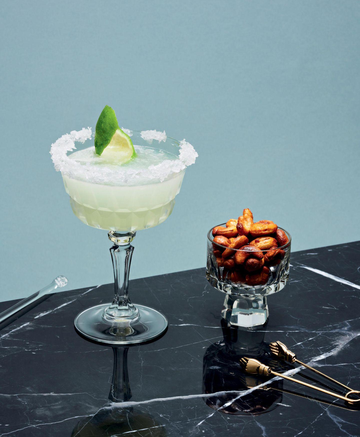 Margarita  für 1 Cocktail:  1 Limette  grobes Salz  6 cl weißer Tequila  2 cl Orangenlikör (z. B. Triple Sec oder Cointreau)  4 cl Limettensaft  gestoßene Eiswürfel  1. Den Rand eines gekühlten Cocktailglases mit einem Limettenschnitz einreiben und in das grobe Salz tauchen. Den Salzrand fest werden lassen.  2. Tequila, Orangenlikör und Limettensaft mit dem gestoßenen Eis in einem Shaker mixen.  3. In das vorbereitete Glas abseihen und mit Limettenschale oder -schnitz dekorieren.  Curry-Cashewkerne  für 4 Personen:  150 ml Ahornsirup  1 EL rote Currypaste  150 ml Wasser  250 g Cashewkerne  1. Ahornsirup, Currypaste und Wasser mit einem Stabmixer fein pürieren.  2. Die Cashewkerne in eine Schüssel füllen und mit dem Curryfond auffüllen.  3. Die Kerne mindestens 4 Stunden ziehen lassen, am besten 24 Stunden.  4. Den Ofen auf 140 °C Umluft vorheizen.  5. Die Kerne abgießen, auf ein mit Backpapier ausgelegtes Backblech geben und ca. 1,5 Stunden im Ofen trocknen lassen.  6. Nach dem Backen die fertigen Kerne auskühlen lassen und luftdicht verpacken.  Hinweis: Luftdicht verpackt halten die Kerne bis zu 2 Wochen.  Zubereitungszeit: 10 Minuten + Warte- und Backzeit