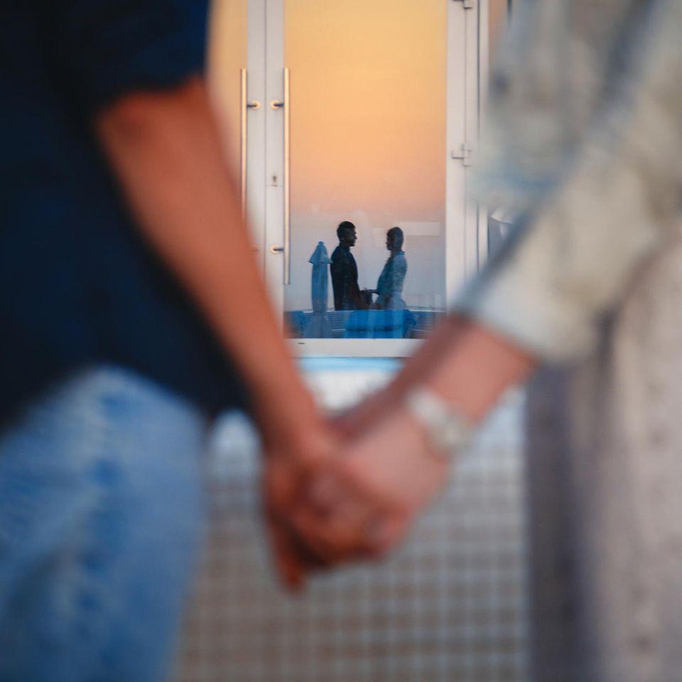 Whisper: Ein Paar steht sich gegenüber, hält sich an den Händen und spiegelt sich in einem  Fenster